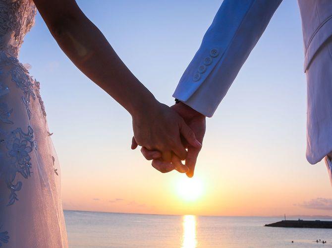 新郎新婦が手を繋いで海に沈む夕日を見ている