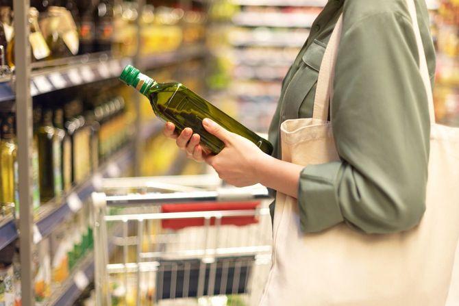 スーパーで油のボトルを確認する女性