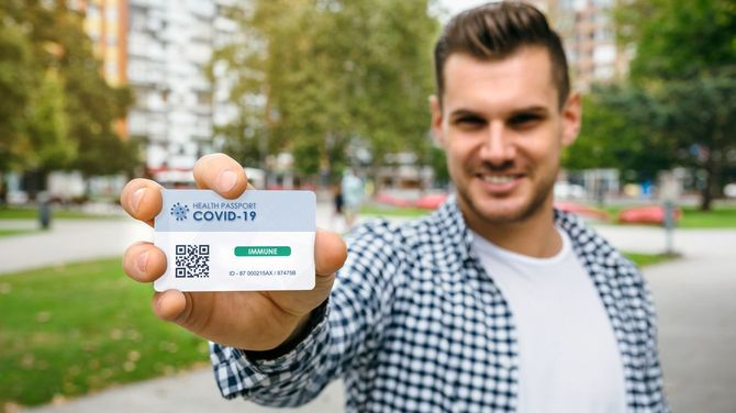 コロナウイルスに免疫があることを示す健康パスポートを示す男性
