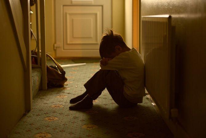 自宅の廊下で膝の間に頭をうずめている悲しげな子供