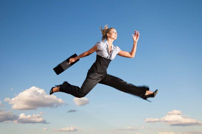 ビジネス鞄を持って空をかける女性