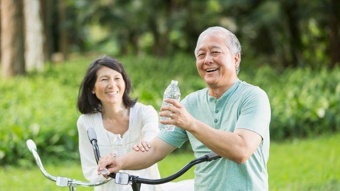 シニアのカップルが手には水のペットボトルを持ち、公園で自転車に乗っている。