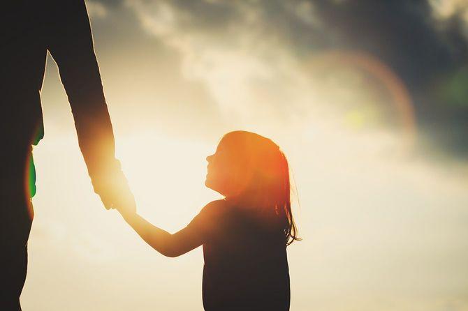 夕暮れ時親の手を握って少女のシルエット