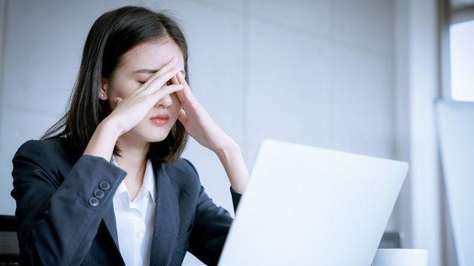 ビジネスウーマンの頭痛の種は、仕事のミスでストレスを感じていたため、解雇されるリスクがある利益損失の問題