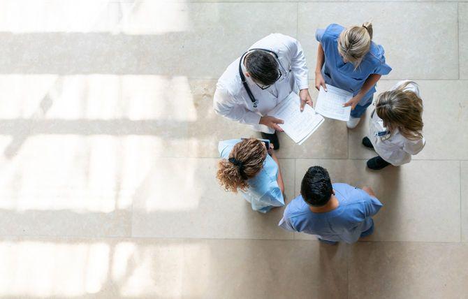病院で立ってミーティング中の医療従事者