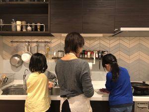 娘たちと食事の準備をする矢上さん(中央)