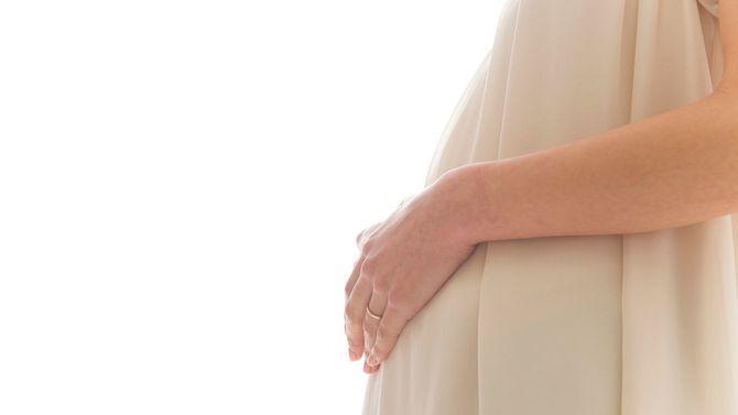 妊婦さんが手をお腹の上に置いている