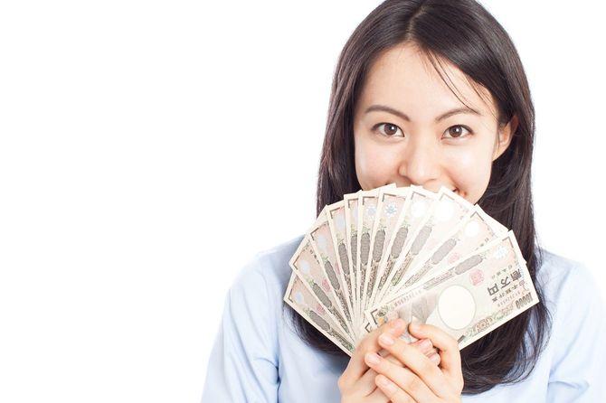 1万円札を広げて持つ女性
