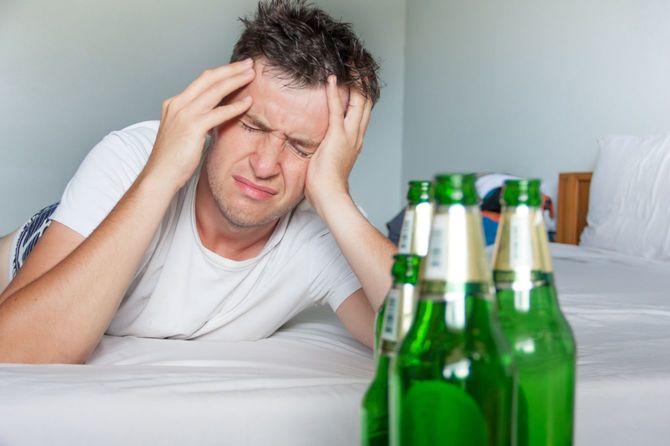 二日酔いの苦しみ男はビールのボトルを持つ肖像画を閉じます。