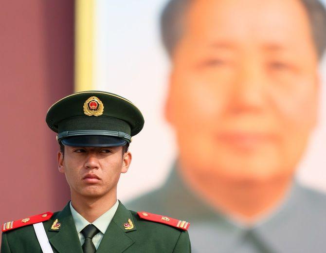 北京の天安門広場にて毛沢東の大きな肖像画の前で警備する中国の警察官
