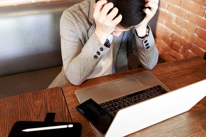 ストレスを感じながらパソコンに向かう男性