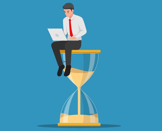 大きな砂時計の上に座って、ノートパソコンで作業しているビジネスマンのイラスト