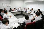 約20名の部員と部長が会議室に集まった。全員着席のまま、部長の話に耳を傾けている。
