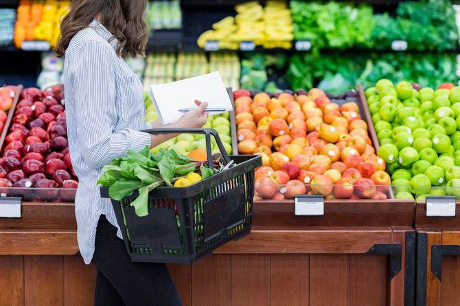 スーパーで野菜や果物を買う女性