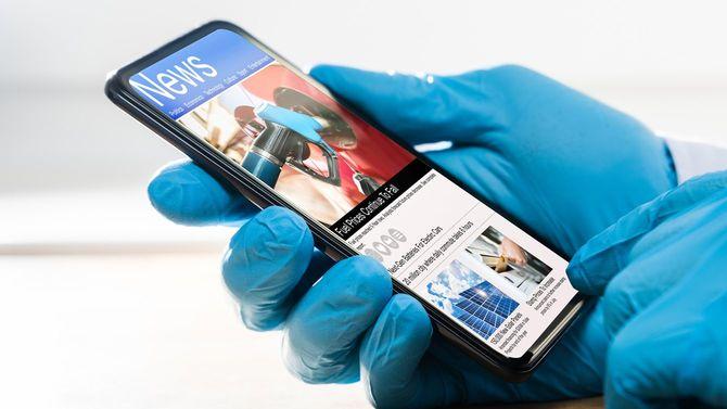 手袋をしたまま携帯電話でコロナウイルスニュースをチェック