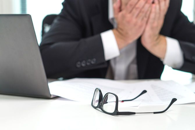 ビジネスマンのオフィスで手で顔を覆っていると強調しました。時間をかけて作業またはあまりにも多く。ビジネスまたは危機の混乱の問題。破産の起業家。燃え尽き症候群と過労。