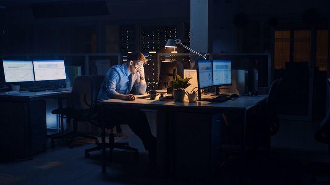 暗いオフィスでデスクに座り目を押さえる男性