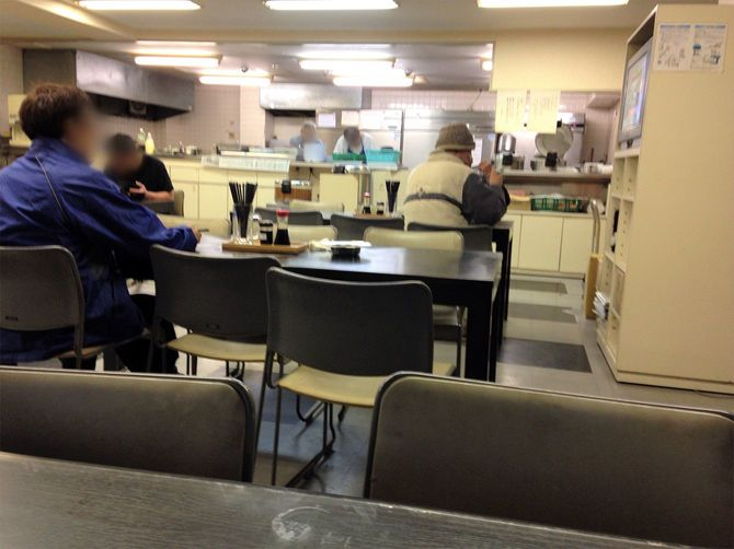 飯場の食堂で夕飯を食べるかっちゃん(右)