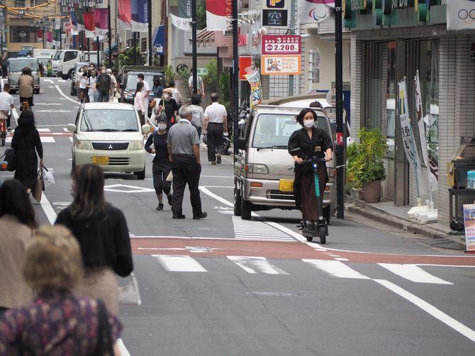 ヘルメットなしで自動車の前を走る電動キックボード