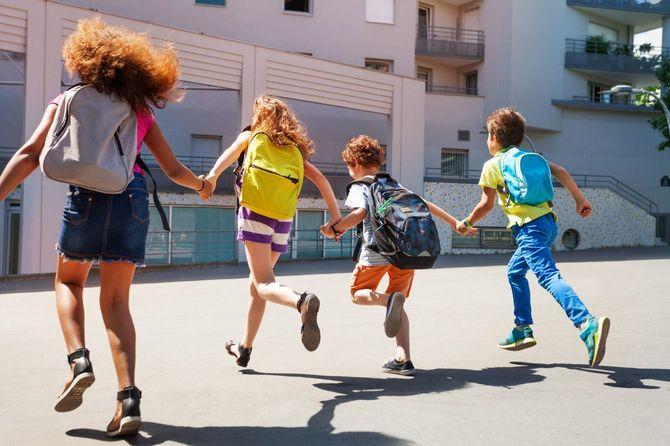 手をつないで学校へ向かうバックパックを背負った子どもたち