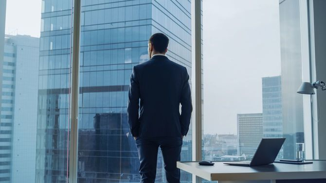 オフィスの窓辺に立ち、外を眺めるビジネスパーソン