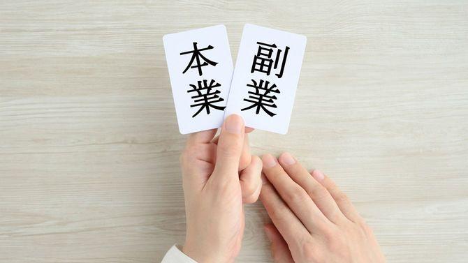 本業と副業のカードを持つ女性の手