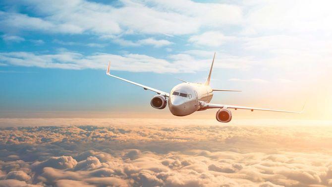 夕陽のなか雲の上を進む飛行機