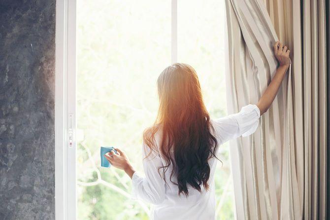 新鮮な空気を得るために朝のカーテンを開ける