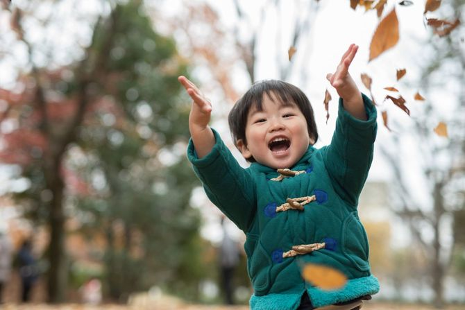秋に紅葉した落葉を舞わせて遊ぶ子供
