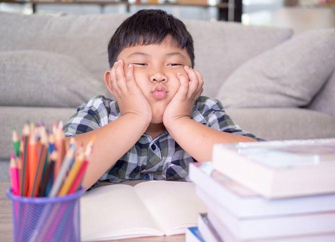 自宅学習に飽きてしまった少年がふてくされている
