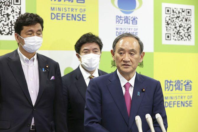 自衛隊が運営する大規模接種センターの視察を終え、記者の質問に答える菅義偉首相(手前)。奥左は岸信夫防衛相、同右は中山泰秀防衛副大臣
