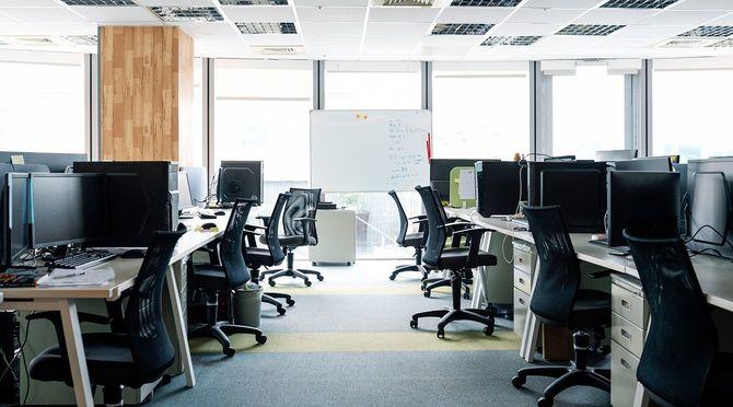 オフィスのデスクで空の椅子とデスクトップPC