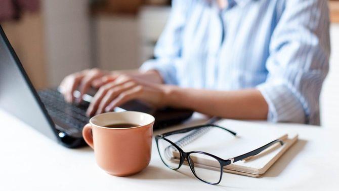 手元にマグカップを置き、ノートパソコンで自宅からリモート作業