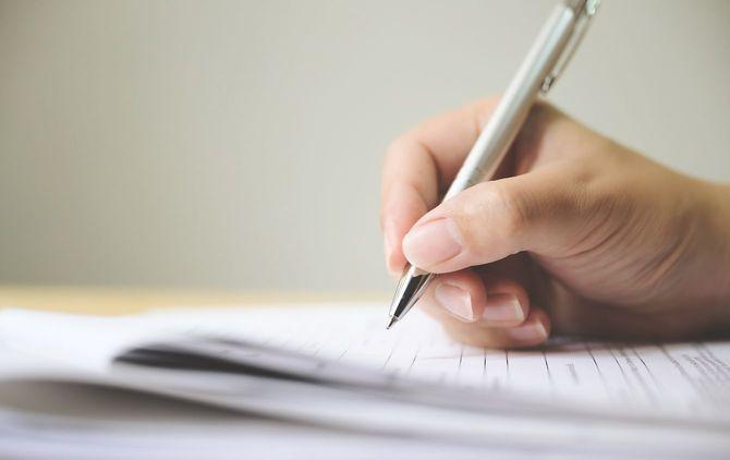 申請書書類に署名署名記入する人の手元