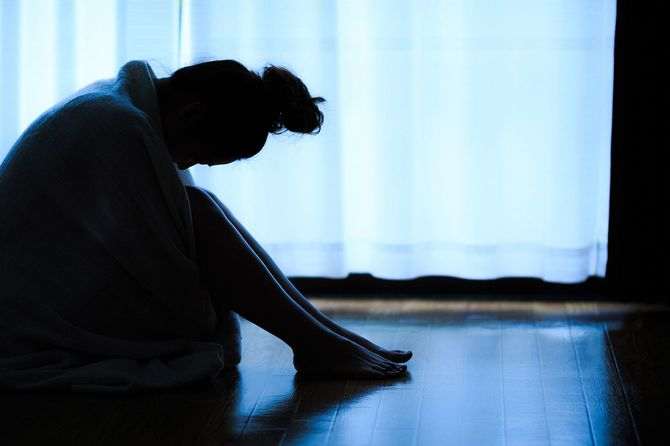 窓際に座って孤独な女性