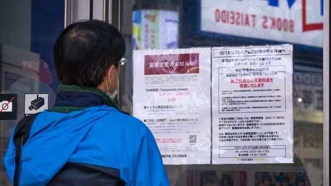 非常事態宣言による業務時間変更の店の通知を見ている日本人男性