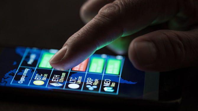 2018年7月25日、スマートフォンのディスプレイで暗号通貨の為替とドルのレートを確認する男性