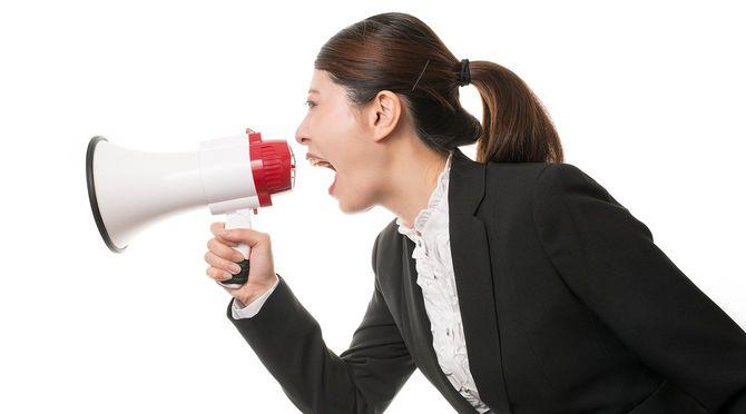 メガホンを使用して叫ぶスーツの女性