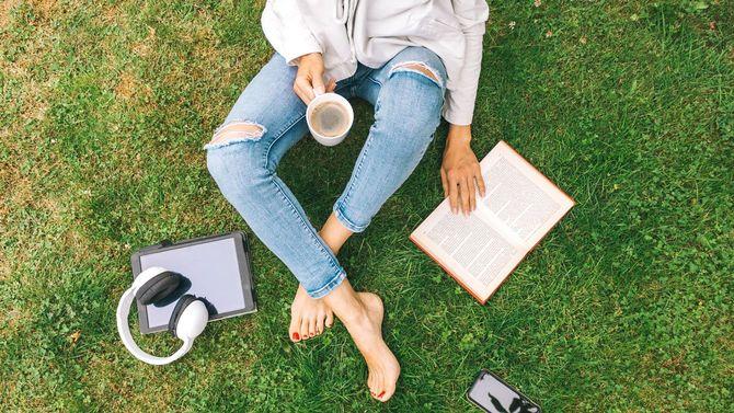 草の上に座っている若い女性はコーヒーを飲みながら本を読んでいる