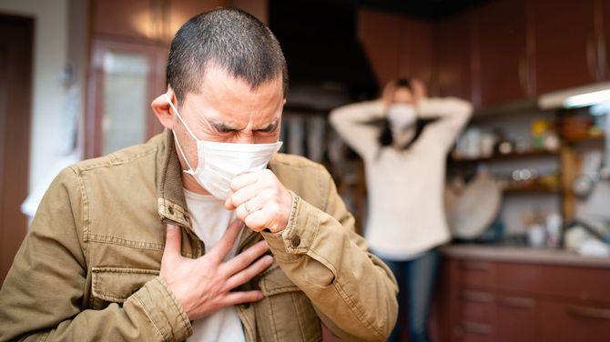 咳をする男性と心配する女性