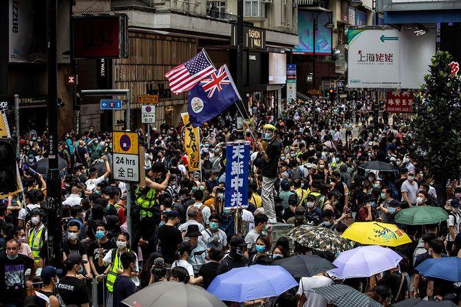 中国政府による香港の国家安全法導入に反対するデモ開始前、米国旗を掲げる参加者=2020年5月24日(中国・香港)