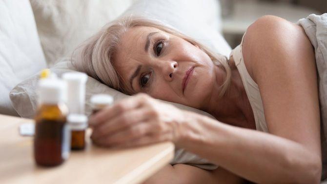 健康的ではない高齢女性がベッドに横たわりながら、サイドテーブルに置かれた数々の薬を見つめている