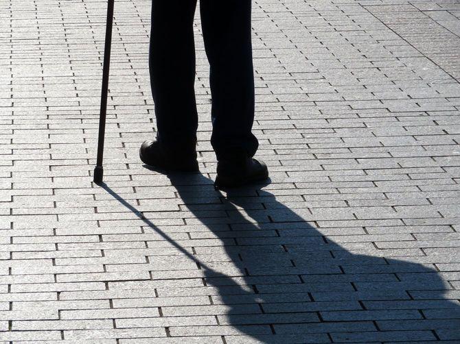 杖をつき歩道を歩く男性の長い影