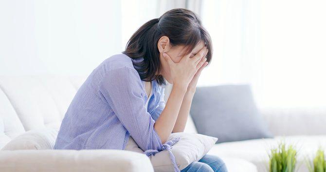 憂鬱な女性が頭を抱えて悩んでいる