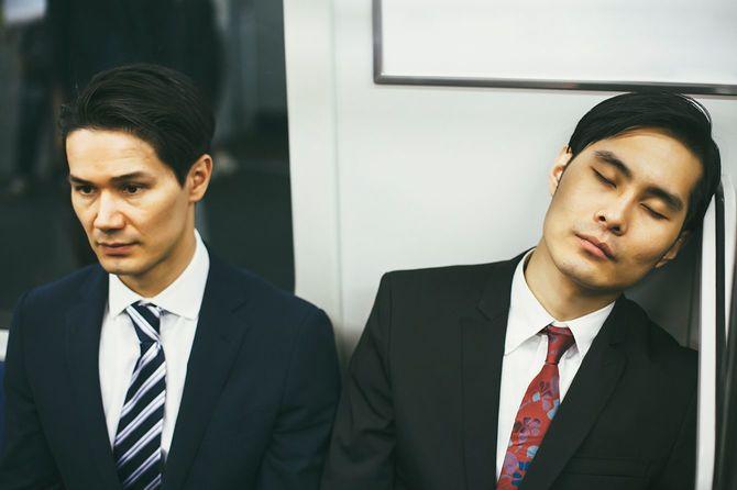 地下鉄で居眠りするビジネスマン