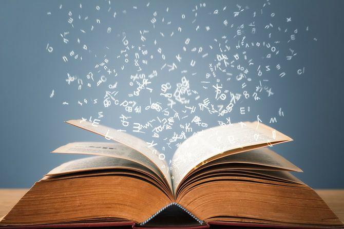個々の文字は、開いた本のページから魔法のように飛ぶ