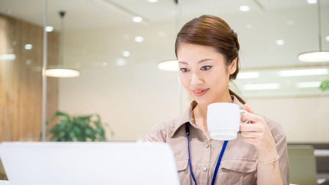 マグカップを片手に席で仕事する女性