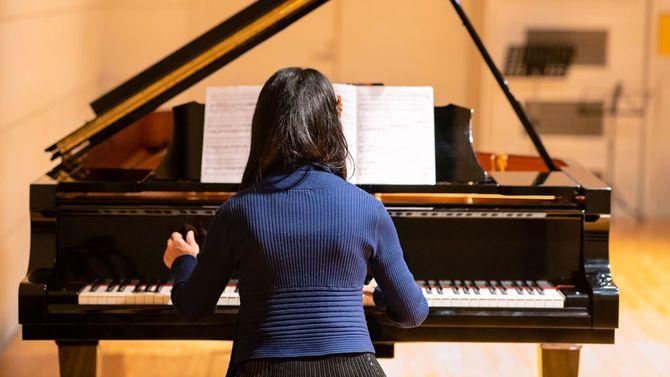 コンサートホールでピアノを弾く女性