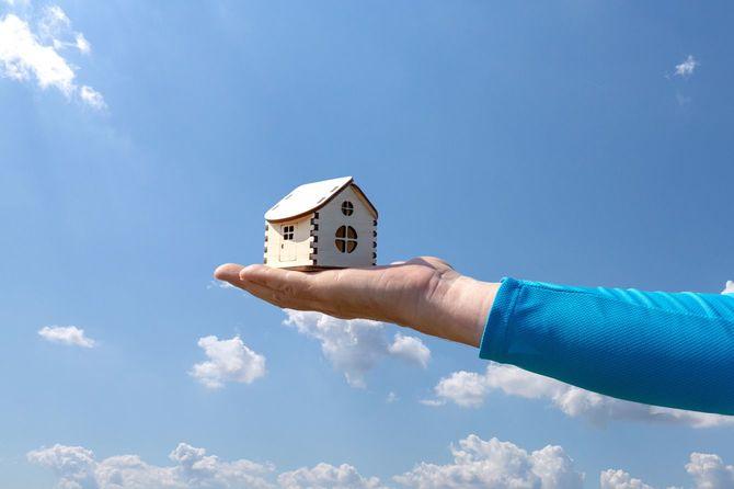 男は手のひらに小さな木造の家を持っている。曇りの空を背景に、手のひらに木造住宅