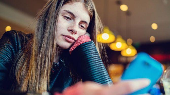 10代の少女がカフェで退屈そうにスマホで文字を打っている